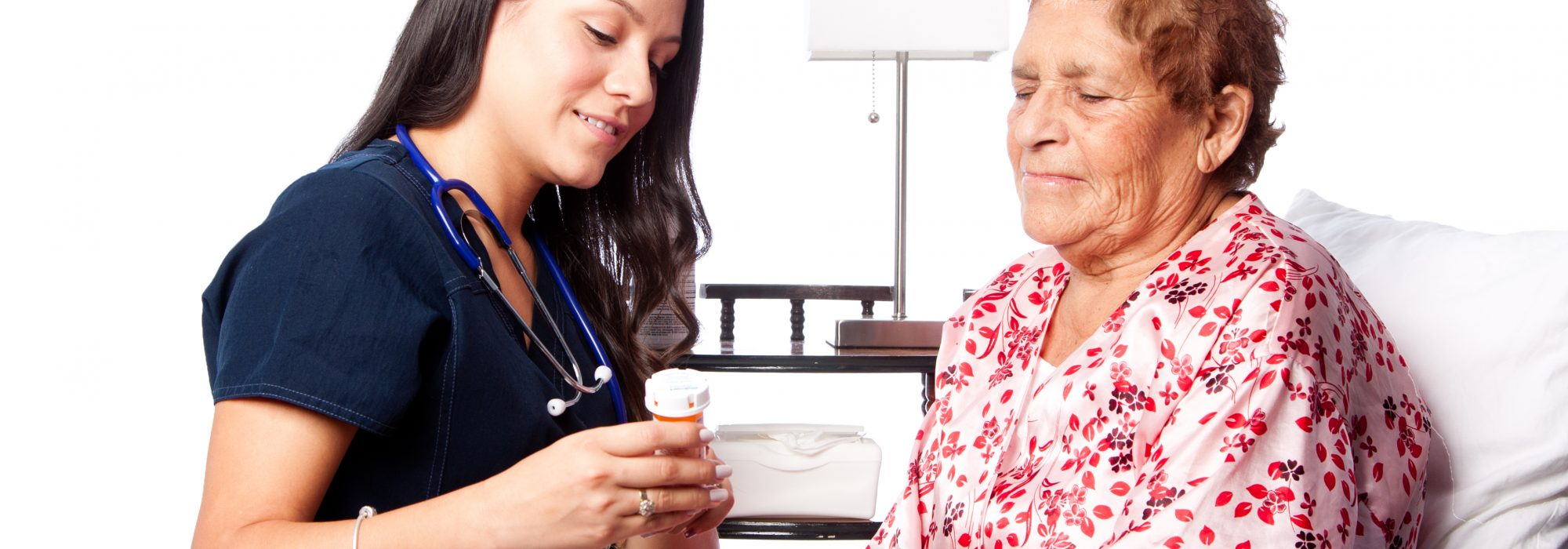 Nurse explaining prescription medication to senior patient, home medical health concept.
